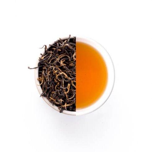 Golden zhenghe kungfu zwarte theebladeren en thee van Mevrouw Cha in een witte theekop.