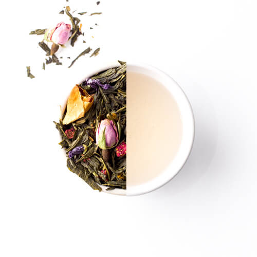 Groene theemelange met rozenknopjes bloemen en aardbeien van Mevrouw Cha, gedroogde verse variant en gezette variant in een witte theekop.