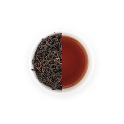 Puerh thee en theebladeren van Mevrouw Cha in een witte theekop.