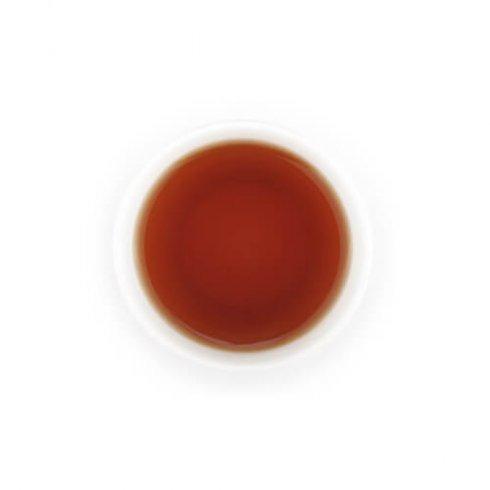 Zwarte thee melange thee in witte theekop.